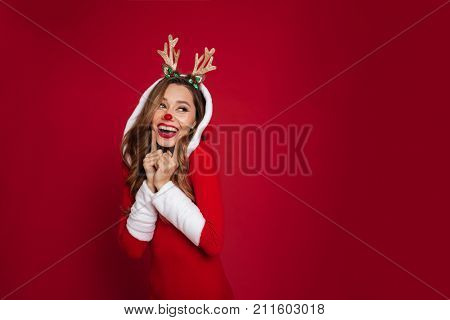 Portrait of a happy laughing girl wearing christmas deer costume while standing and looking away isolated over red background