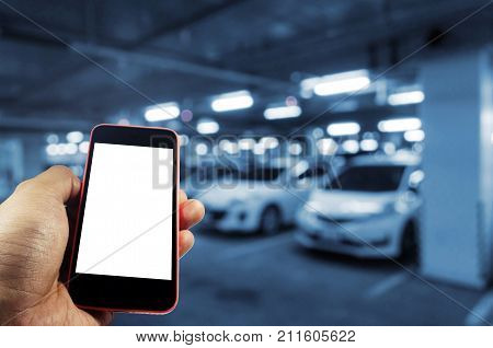 hand using mobile smart phone with blank screen for text with blurred image of underground car parking garage area background internet technology and searching information concept blue color tone