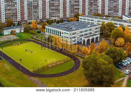 City landscape with a school and a football field in autumn in Moscow, Russia