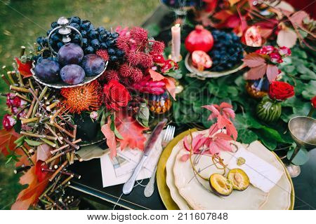 The festive wedding table with red autumn leaves. Wedding decoration. Artwork Close-up