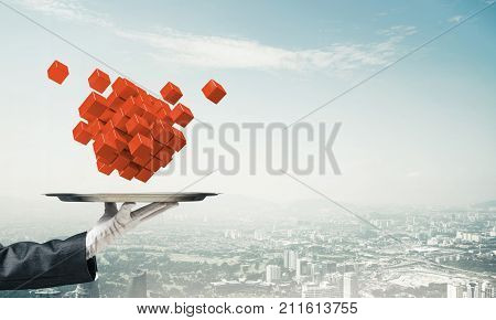 Cropped image of waiter's hand in white glove presenting multiple cubes on metal tray with cityscape view on background.