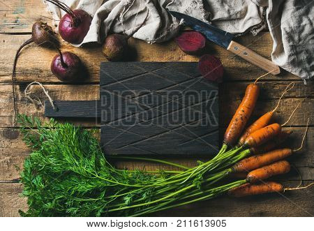 Healthy food cooking background. Vegetable ingredients. Fresh garden carrots and beetroots on rustic wooden background with dark cutting board in center, top view, copy space