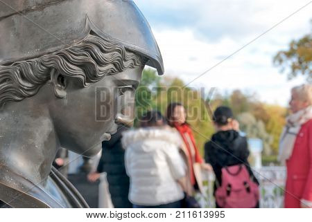 TSARSKOYE SELO, SAINT-PETERSBURG, RUSSIA - OCTOBER 7, 2017: People walk on The Cameron Gallery near the bronze busts of the Antique deities, heroes and great names of history. Minerva Sculpture