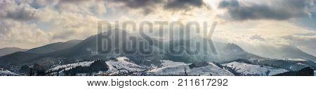 Mountain Ridge In Light Beams On Cloudy Winter Day