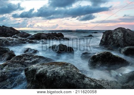 Waves in long exposure in the ocean at sunset at Koh Lanta with Stones in the sea and Phi Phi islands in the horizon, Koh Lanta, Thailand, Asia