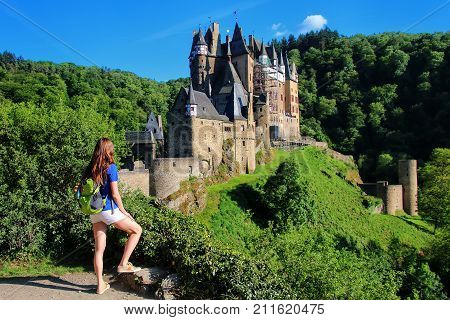 Young woman standing at the overlook of Eltz Castle in Rhineland-Palatinate Germany. It was built in the 12th century and has never been destroyed.