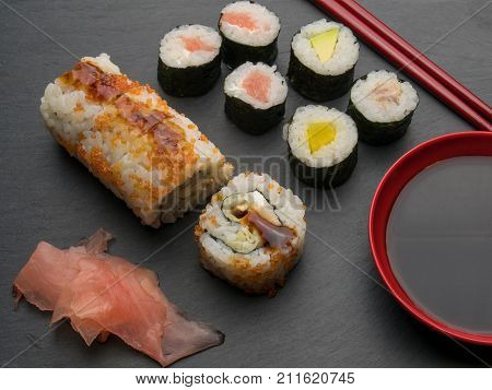 Japanese Sushi - Kappa Maki Sushi Roll with Soy Sauce and Ginger over Stone Background. Top View.