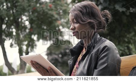 Laughing Young African American Female Holding a Touch Pad Tablet PC Outdoor