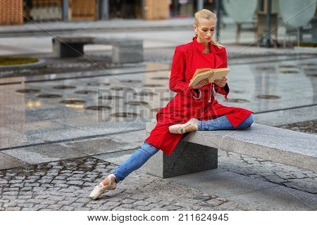 Ballerina Sit On The Bench.young Beautiful Ballerina In Red Coat And Pointe Shoes Rest Outdoors.