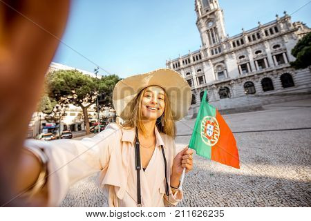 Young woman tourist making selfie photo with portuguese flag in front of the city hall building during the morning light in Porto, Portugal