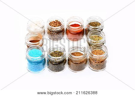 Set of seasoning making frame. Herbs and spices concept. Glass containers with paprika salt blue sea salt french mustard dry oregano basil and curry. Jars of spices isolated on white background.