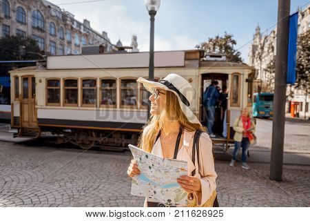 Lifestyle portrait of a woman with paper map near the famous old touristic tram on the street in Porto city, Portugal