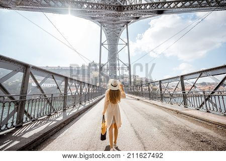 View on the famous Luis bridge with woman walking during the foggy and windy weather in Porto city, Portugal