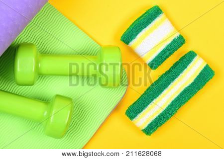 Dumbbells Made Of Plastic On Wavy Green And Yellow Background