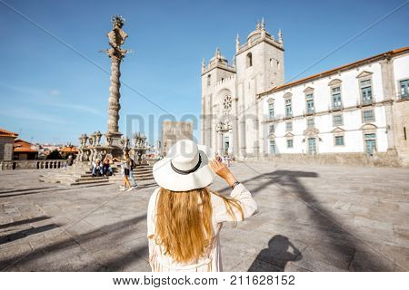 Young woman tourist in sunhat standing back in front of the main cathedral in Porto city in Portugal