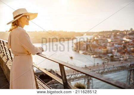 Young woman tourist enjoying beautiful aerial cityscape view with famous bridge during the sunset in Porto city, Portugal