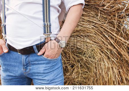 A Man In Blue Jeans And A White Shirt With Suspenders In The Background Of A Haystack