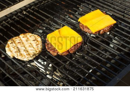 Cutlet minced meat Burger fried and grilled bacon. Preparation of ingredients for a hamburger. Round patties of raw minced meat roasted on a metal grid.