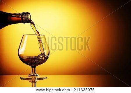 pouring a glass of cognac against orange gradient