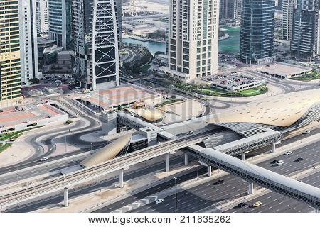 DUBAI, UAE - JAN 13, 2017: Metro station Tower Lake Jumeirah, Indigo Tower and highway, Dubai Metro was opened in 2009