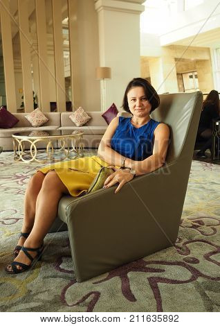 An adult woman in fashionable clothes sits in a chair in the hotel lobby