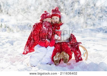 Kids Sledding In Winter Forest. Children Drink Hot Cocoa In Snow.