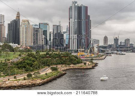 Sydney Australia - March 21 2017: Green zone Millers Point with Barangaroo Reserve and Stargazer Lawn under heavy gray cloudscape in front of skyline of highrise office buildings. Darling Harbour and HSBC tower dominates.