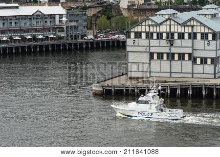 Sydney Australia - March 21 2017: White Harbor Patrol Police boat patrols in front of historic piers now converted into housing and offices at Dawes Point.