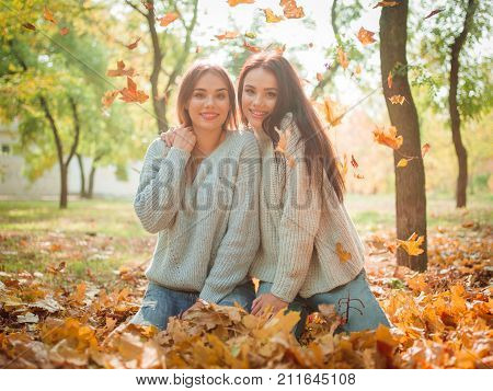 Close-up of beautiful girls, sisters, in an autumn park of warm sweaters, sitting on a blanket in an autumn park toss leaves. The family, sisters, relationship.