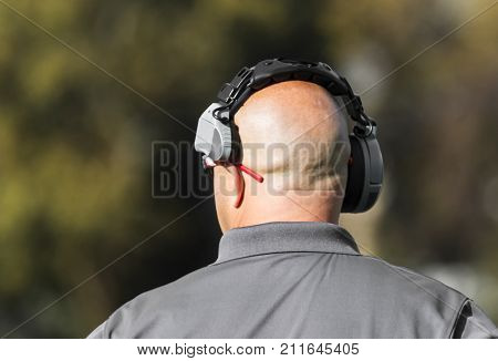 A high school football coach has his headset on while looking down the field at the play being run by his team.