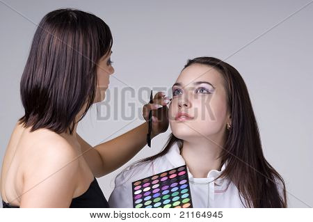 Beautiful young woman dong makeup on a gray background closeup poster