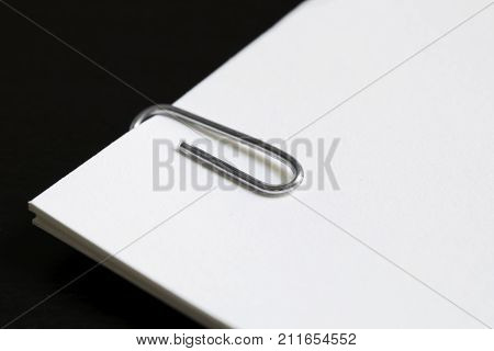 Paperclip on white paper on top of a black desk