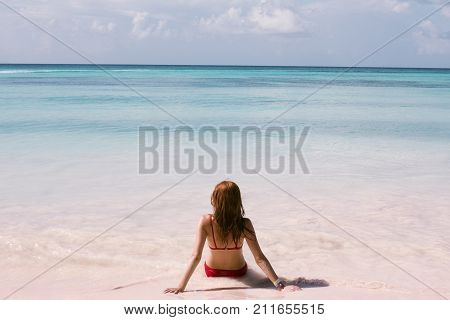 Beautiful young woman is sitting on sand, tropical beach in dominican republic
