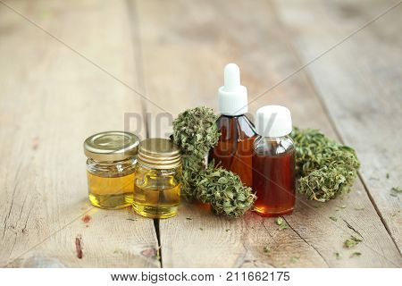 Alternative Medicine Green Leaves Of Medicinal Cannabis With Extract Oil On A Wooden Table
