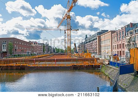 AMSTERDAM HOLLAND- AUGUST 19 2017; Cranes on platform over canal with water sealed out building and under-canal carpark