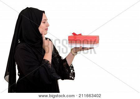 Happy young muslim woman with shopping bag and gift boxes isolated over white background.