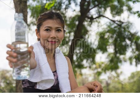 Young woman wearing sport wear giving drinking water bottle forward. sweaty thirsty resting break time. Sport healthy girl after fitness exercise workout training outdoors. Selective focus on face.