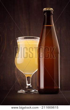 Brown beer bottle NRW and glass tulip with muddy weizen on dark wood board vertical mock up. Template for advertising design branding identity.