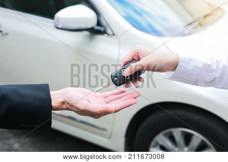 Closeup of a female car owner giving car keys from the car dealer.