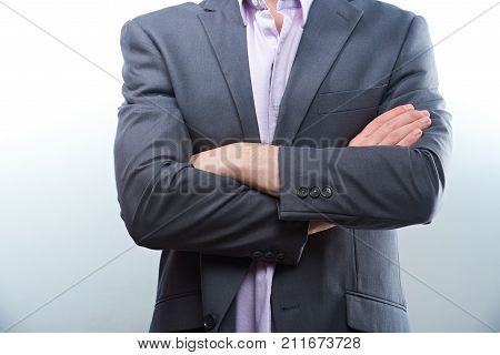 Man in gray jacket suit with crossed arms closeup isolated on white background