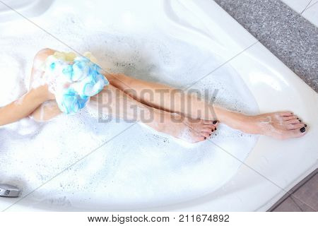 Beautiful young woman taking a shower. Hot bath tub and rest for her legs.