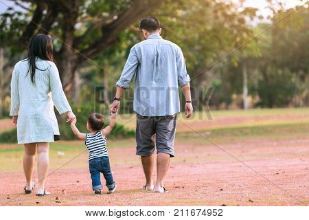 Father and Mother with son holding hand in hand in spring.