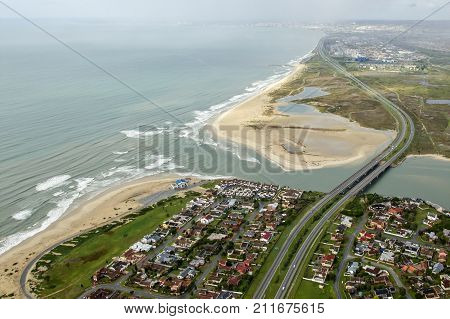 Swartkops river estuary in Port Elizabeth south africa from the air with a dual lane high way running across it in rainy weather