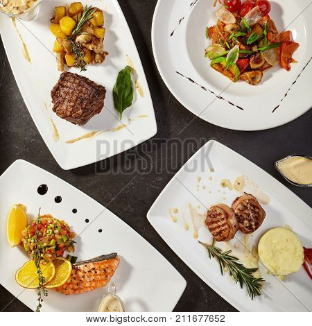 Set of main dishes with fish, meat and vegetables with greens fried on grill