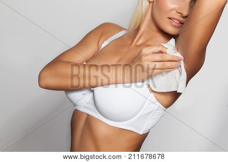 Young woman wiping the armpit with wet wipes, perspiration, sweat