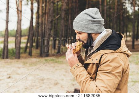 hungry young man eating sandwich outdoors in forest