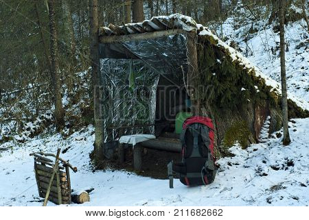 Improvised deliberately primitive lean-to shelter from poles bark and branches in the winter snow-covered forest. In the foreground is a red modern backpack.