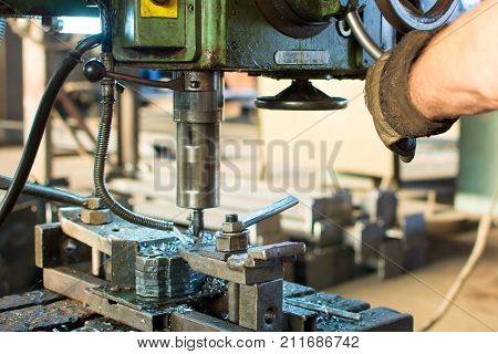 Worker Operating Stainless Steel Drilling Machine