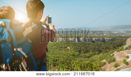 Young father with little son traveling in antic town in crimea. Baby sits in backpack on the shoulders of his dad. Man doing photos by the phone.
