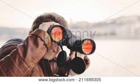 Little caucasian boy watching looking gazing searching for by binoculars during trip toothy smile